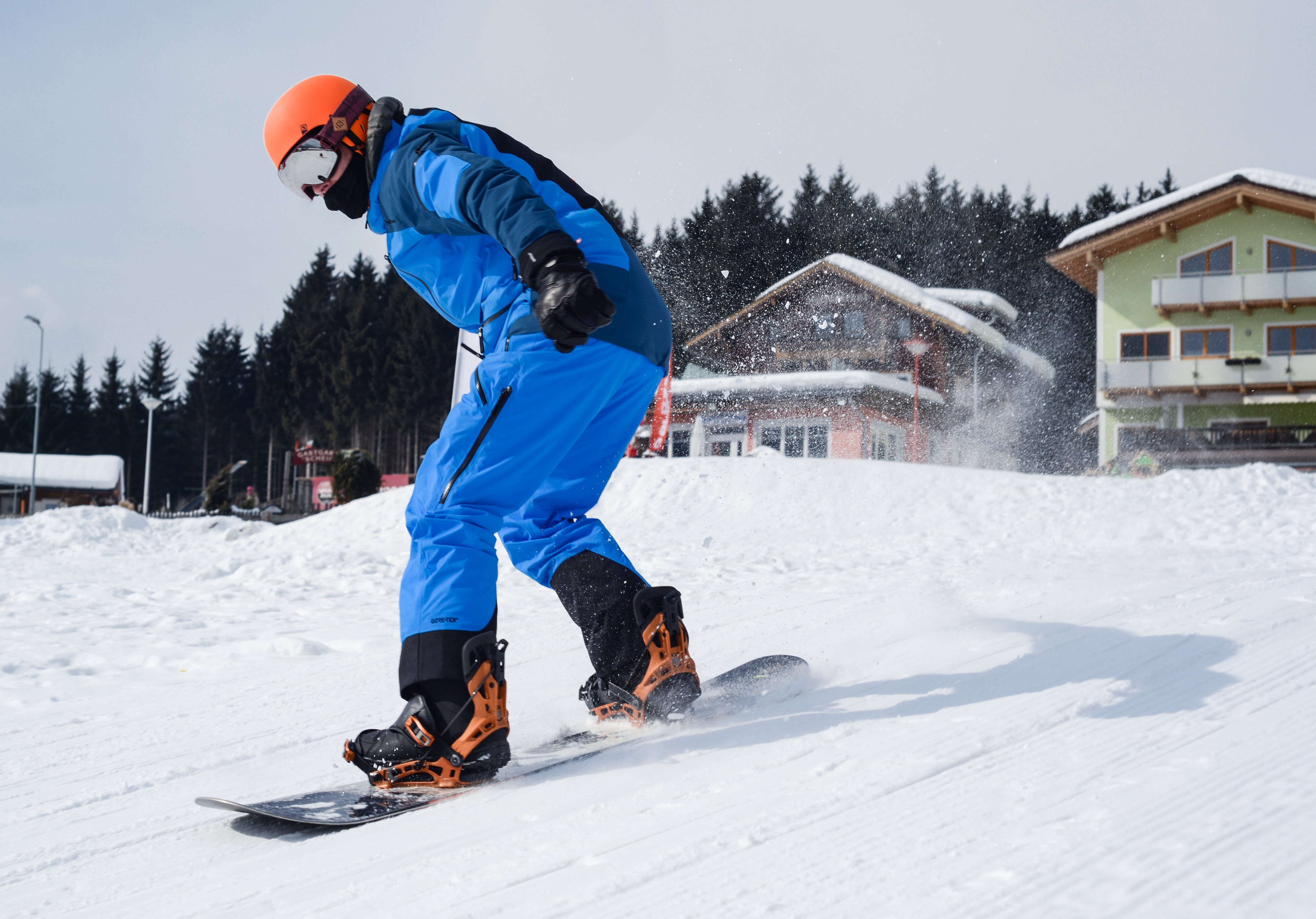 Person in Blue Coveralls Snowboarding on Snow