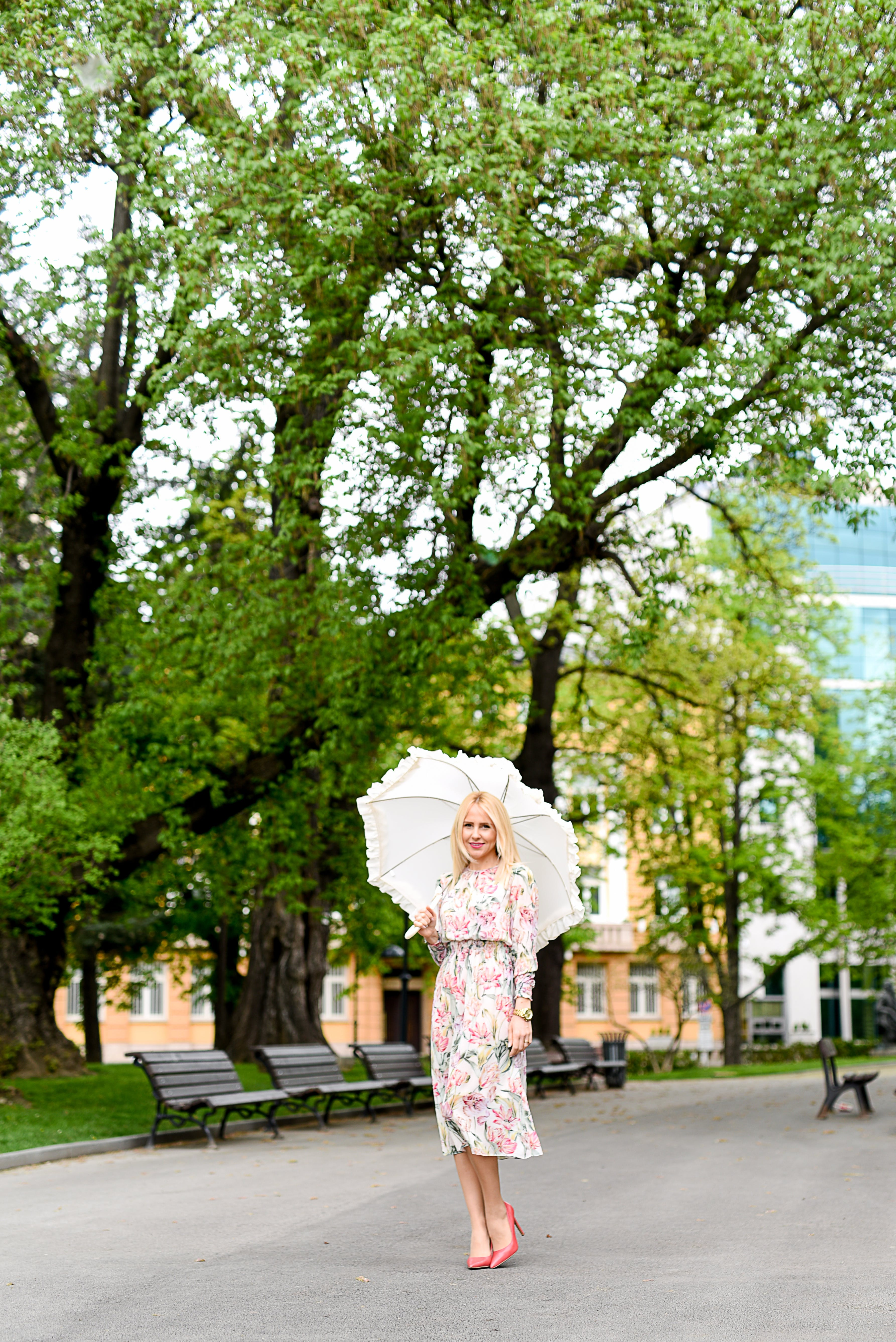Woman in White Green and Red Floral Holding White Umbrella on Gray Concrete Pathway Near Brown Wooden Bench Near Trees during Daytime