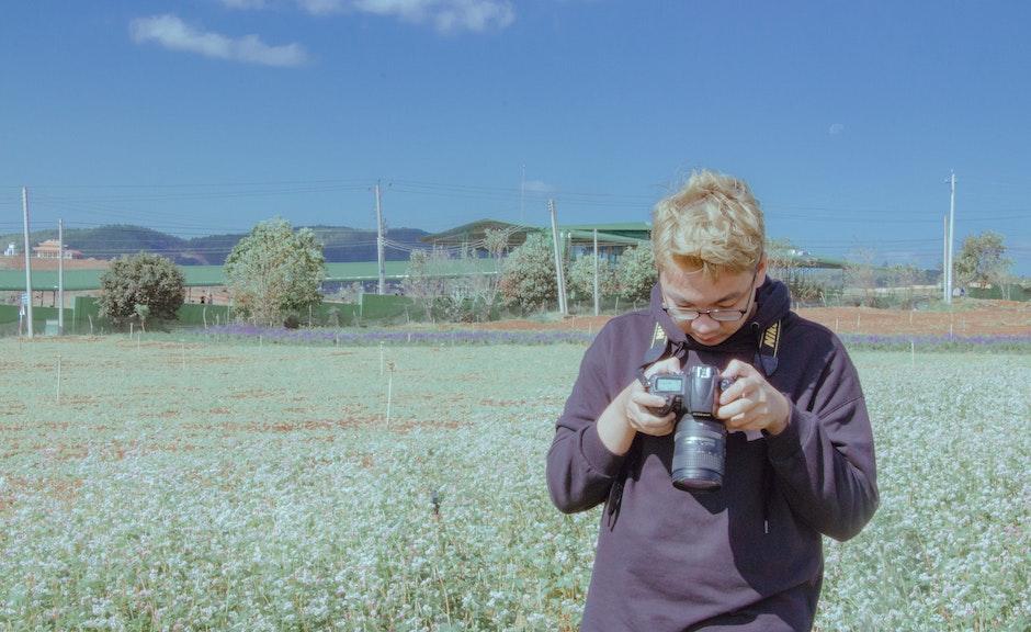 Man Holding Black Dslr Camera Under Blue Sky