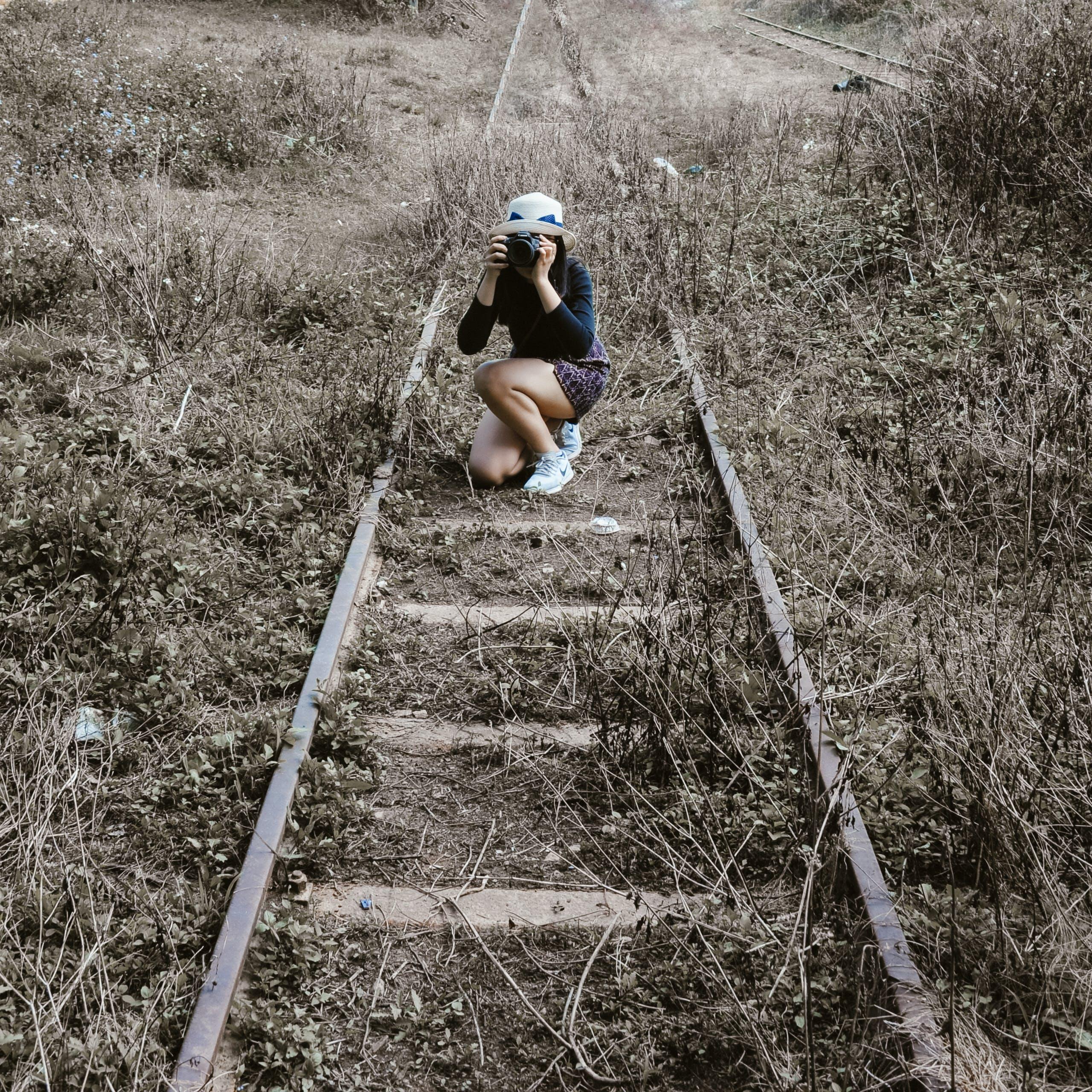 Woman White Round Hat Holding Black Dslr Camera on Rail Way