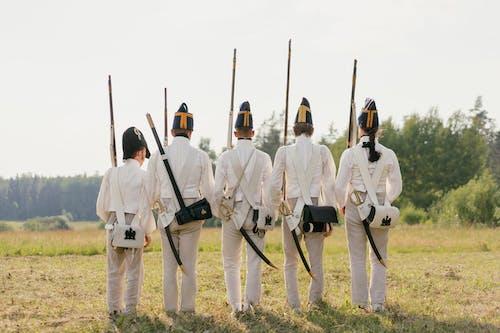 Men in White Uniform Holding Rifle