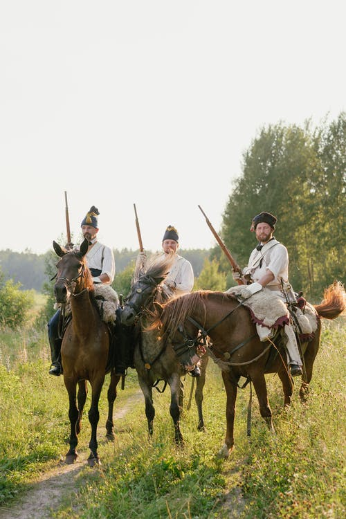 Men Riding Horses Holding Rifles