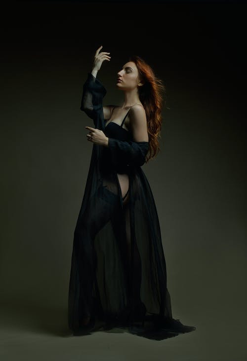 Woman in Black Sleeveless Dress Holding Black Wireless Microphone