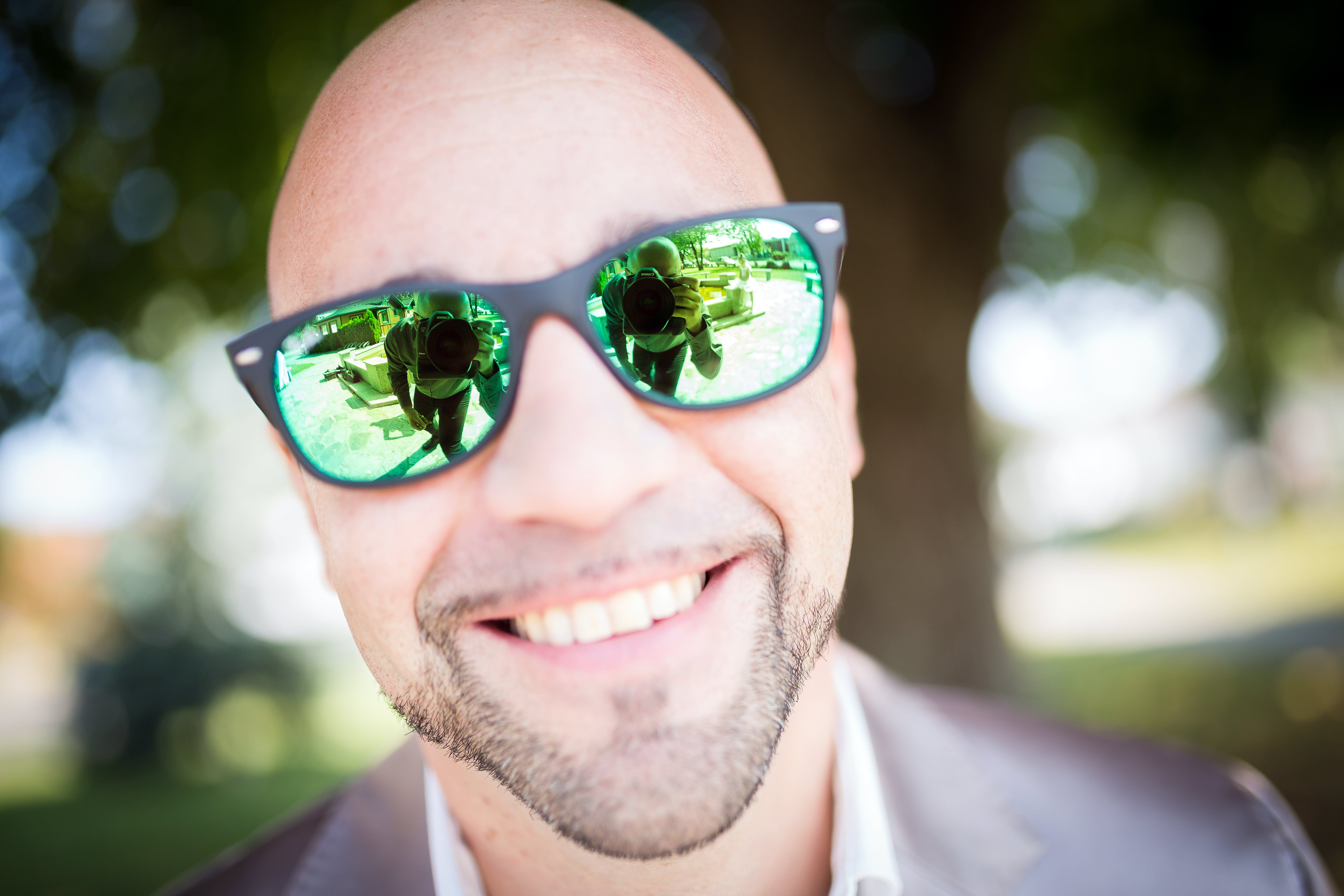 Shallow Focus Photography of Man in Gray Top Wearing Green Sunglasses With Black Frames