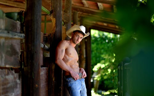 Topless Man Wearing Blue Denim Jeans and White Cowboy Hat Sitting on Brown Wooden Fence during