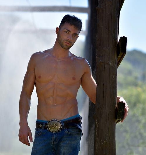 Topless Man Wearing Blue Denim Bottoms and Black Leather Belt Standing Beside Brown Wooden Post during