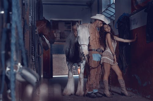 Woman in White Cowboy Hat Riding Brown Horse