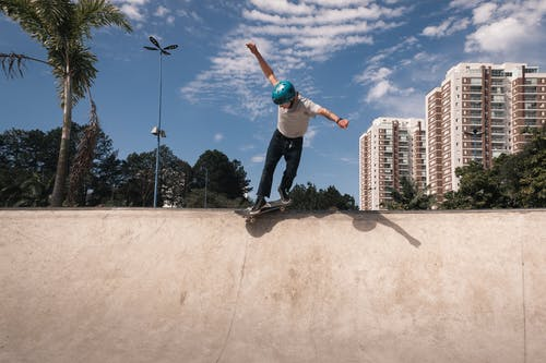 Man in Blue T-shirt and Black Pants Doing Skateboard Stunts on Gray Concrete Floor during