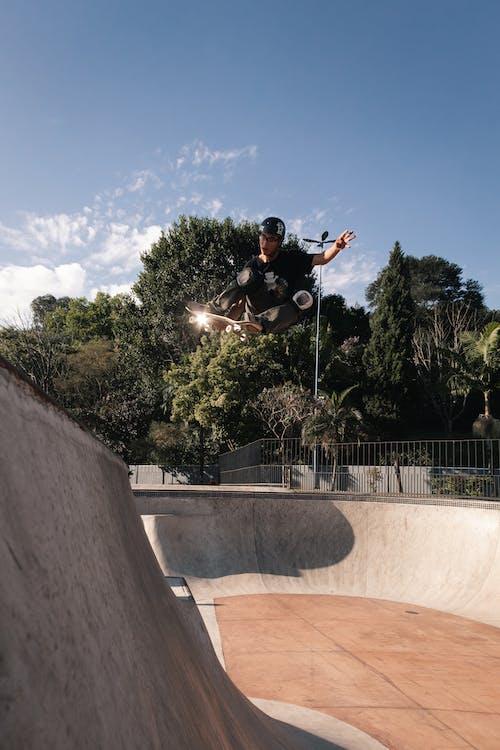 Man in Black T-shirt Riding a Skateboard