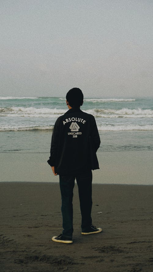 Man Wearing a Jacket Standing on the Beach