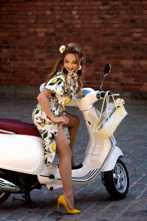 Woman in White and Brown Floral Dress Sitting on White and Red Motor Scooter