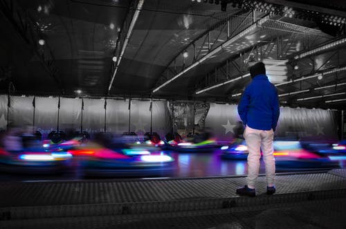 Man in Blue Jacket Staring at Bumper Cars