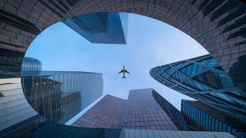 Airplane Flying over the High Rise Building