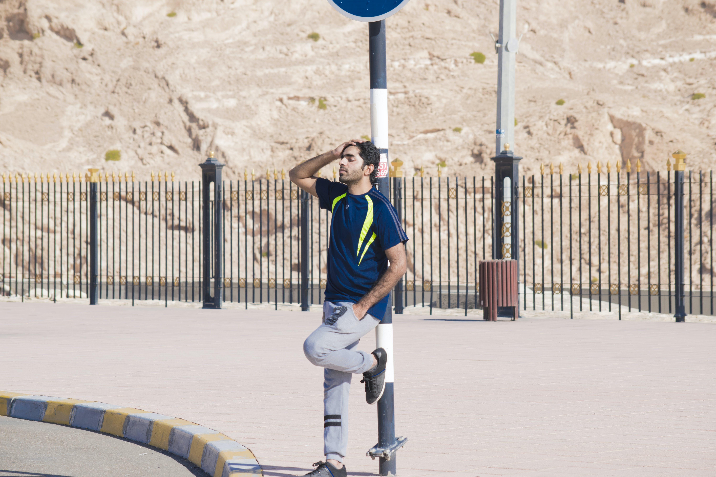 Man Wearing Blue Crew-neck Shirt Leaning on Street Post