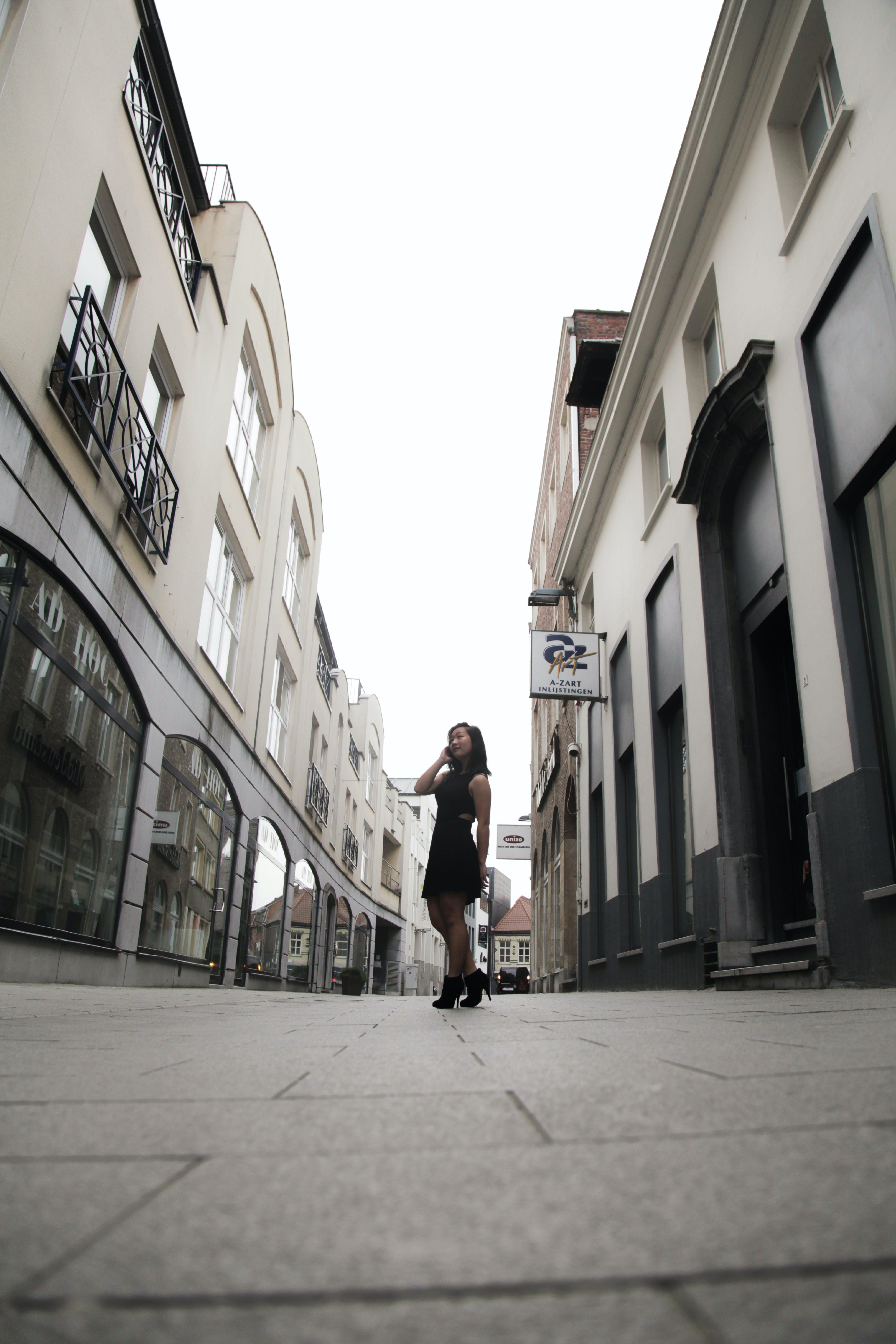 Woman Wearing Black Sleeveless Dress in Between Buildings