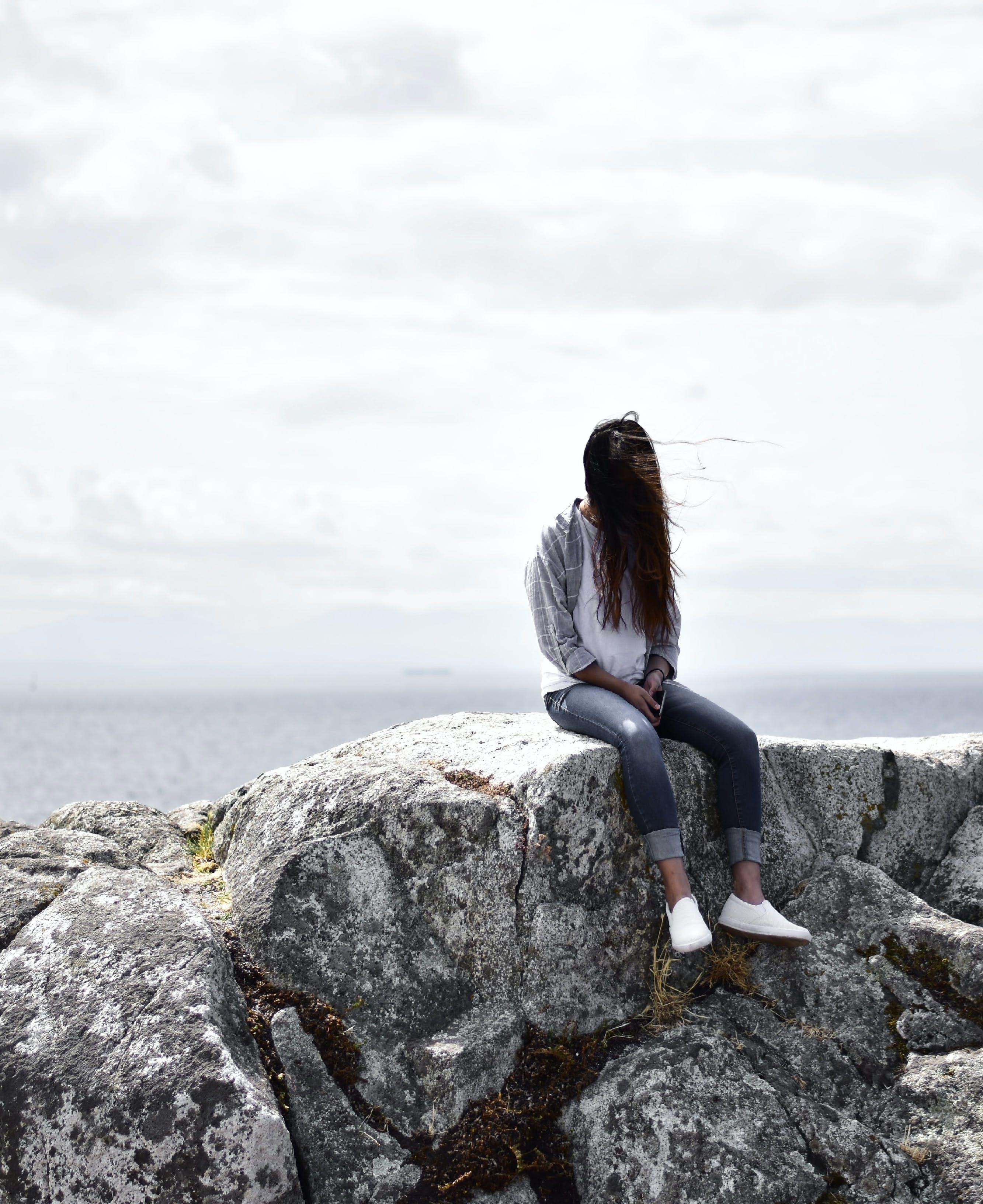 Woman Sits on Gray Rock