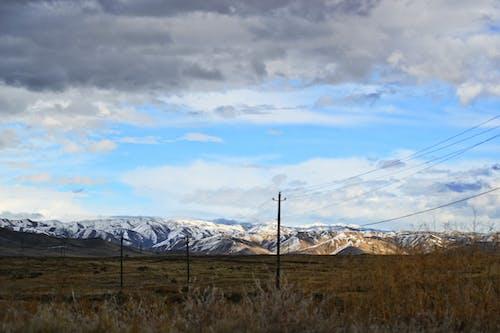 Immagine gratuita di campo, catena montuosa, linee elettriche, montagne