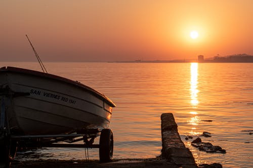 White and Blue Boat on Shore during Sunset