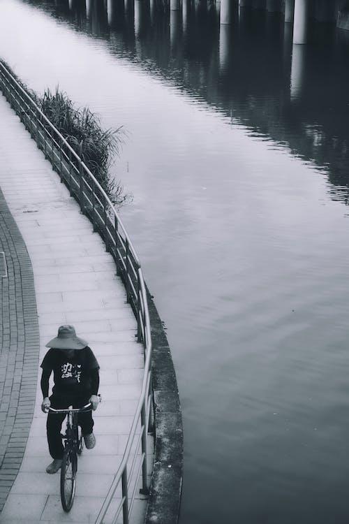 Man in Black Jacket and Black Pants Walking on Gray Concrete Bridge