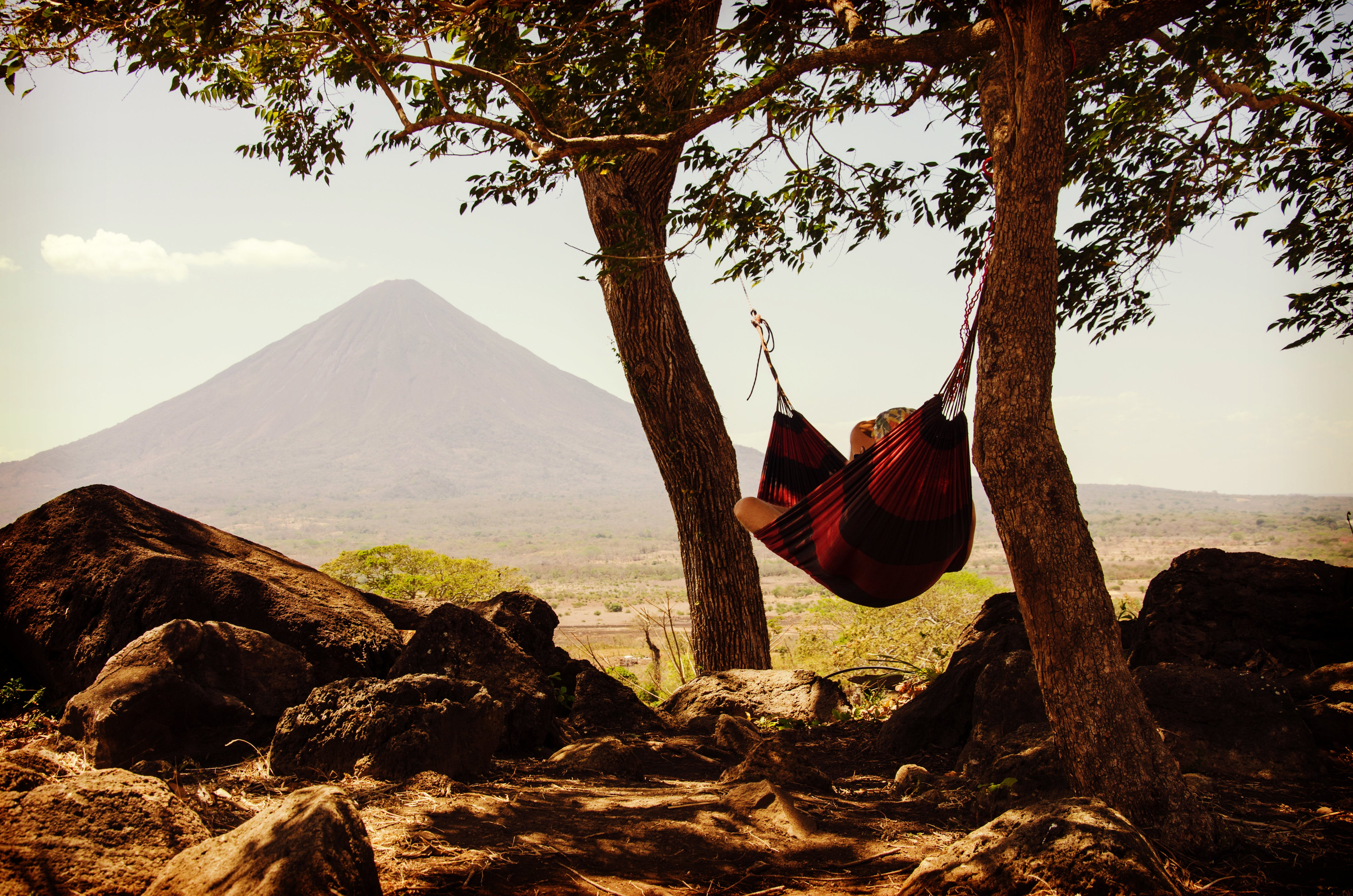 Person Lying on Black and Red Hammock Beside Mountain Under White Cloudy Sky during Daytime