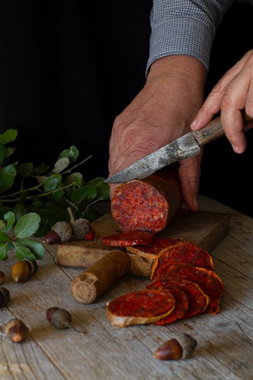 A Person Cutting Processed Meat on a Wooden Chopping Board