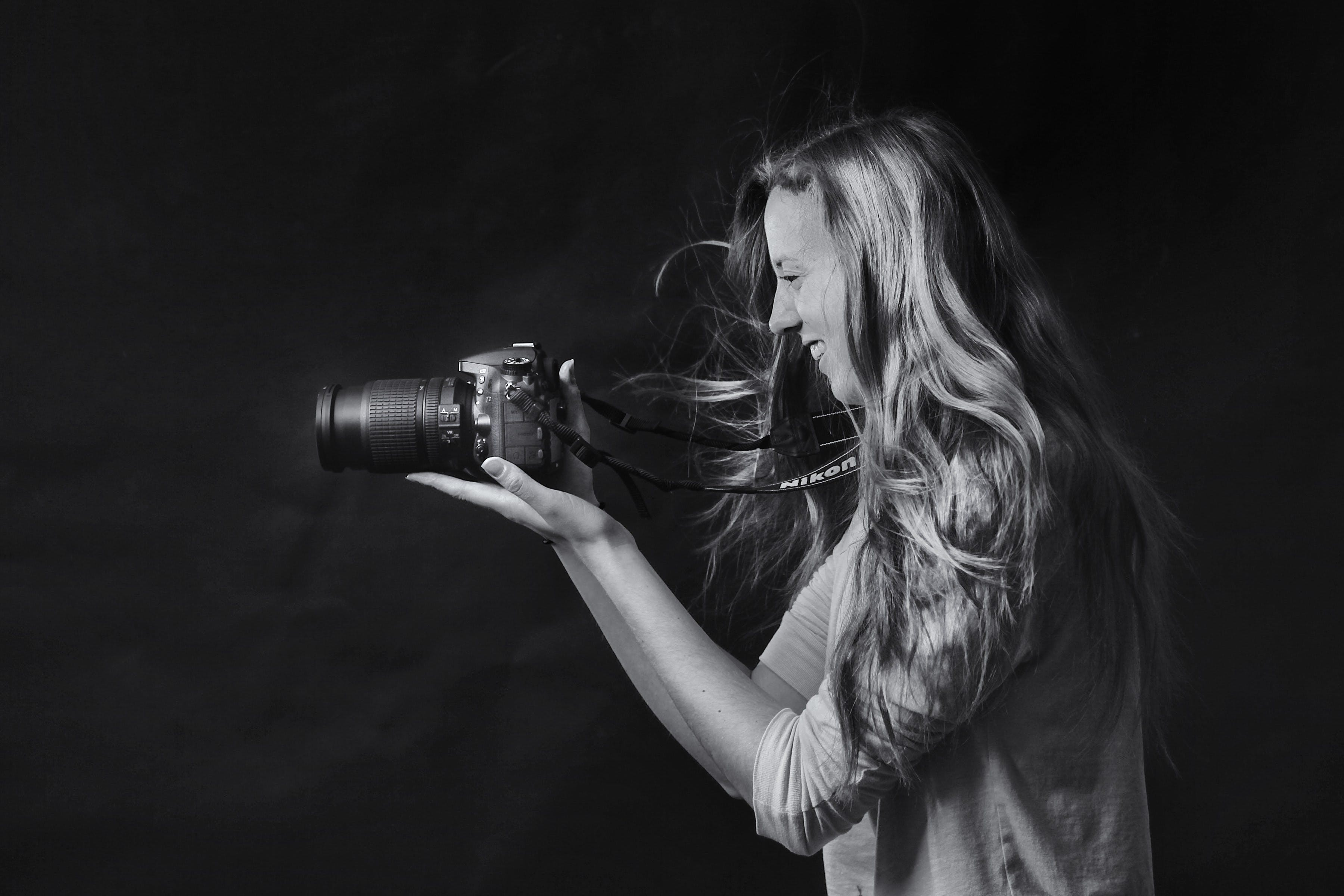 Grayscale Photo of Woman Using Dslr Camera