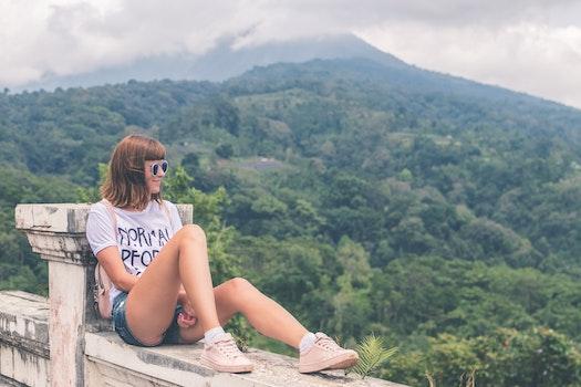 Woman in White Shirt and Blue Denim Short Shorts Sitting