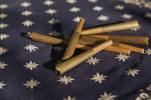 Brown Wooden Sticks on Blue and White Floral Textile