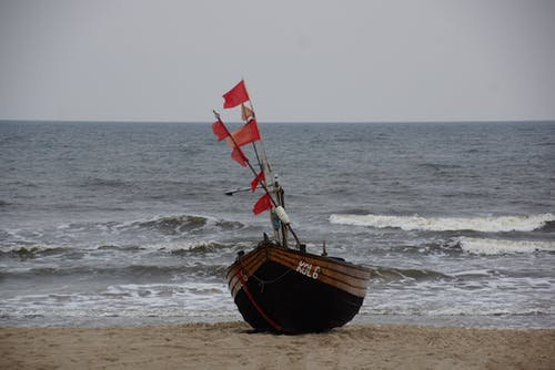 Brown Boat with Red Flags on the Seashore