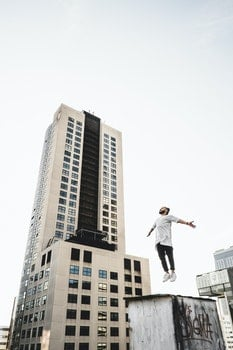 Man Wearing White Long Sleeve Shirt Beside White and Black High Rise Building