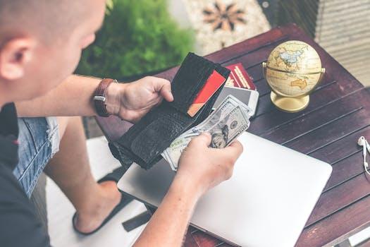 Man Holding U.s Dollar Banknotes and Black Leather Bi-fold Wallet