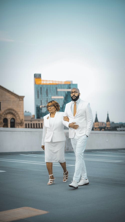 Man in White Suit Standing Beside Woman in White Dress
