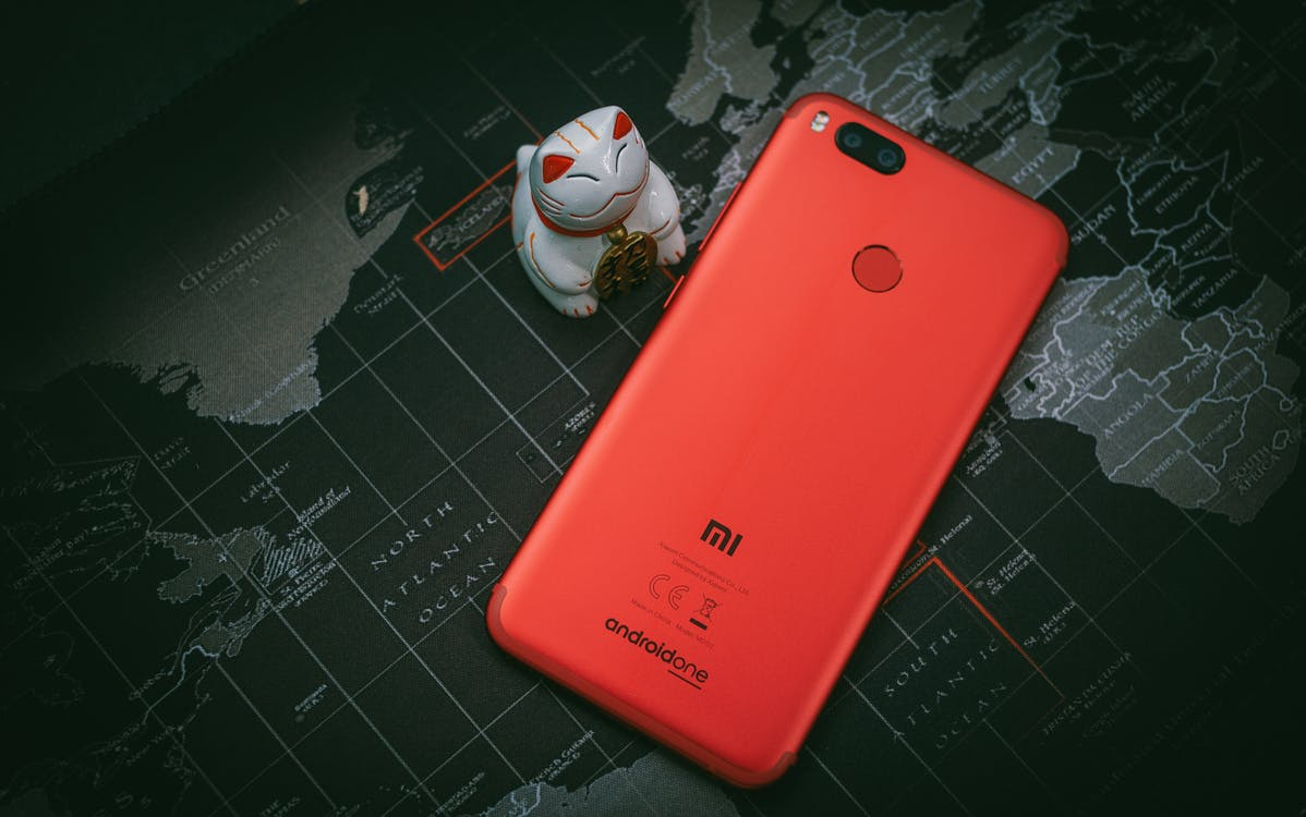 Red Xiaomi Mi Smartphone Beside White Cat Figurine