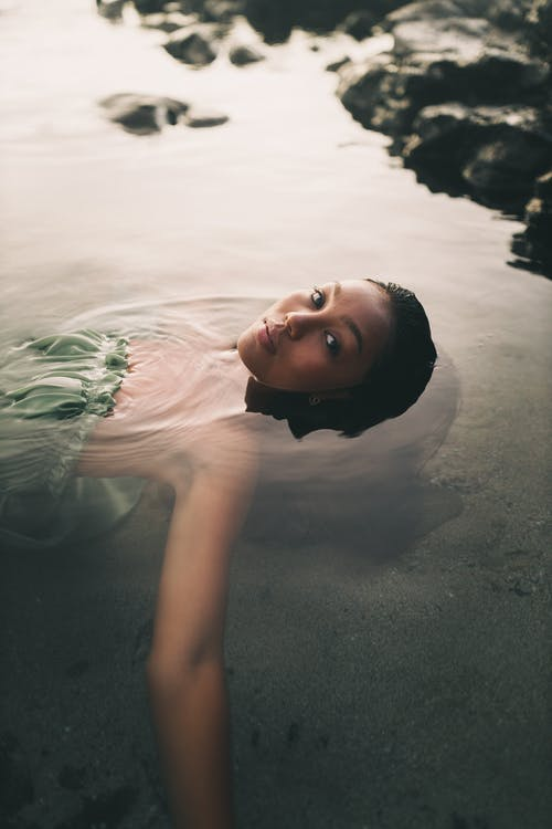 A Woman in a Green Dress Floating on the Water