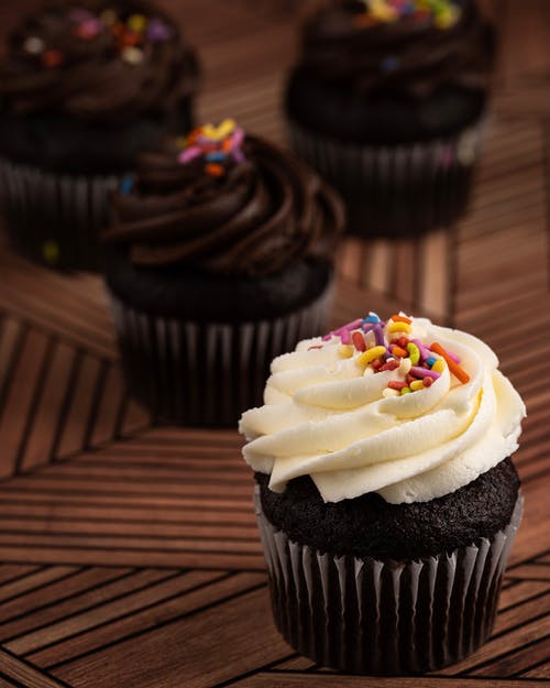 Close-Up Photo of a Chocolate Cupcake with Icing and Sprinkles on Top