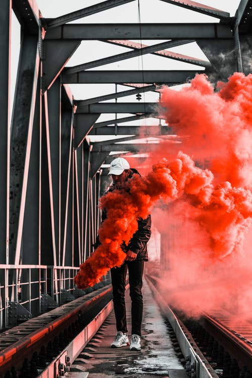 Man in Black Jacket Holding Red Smoke on Metal Bridge