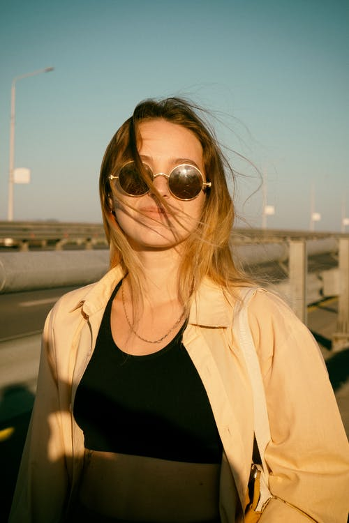 A Cheerful Woman in Sunglasses and Overshirt