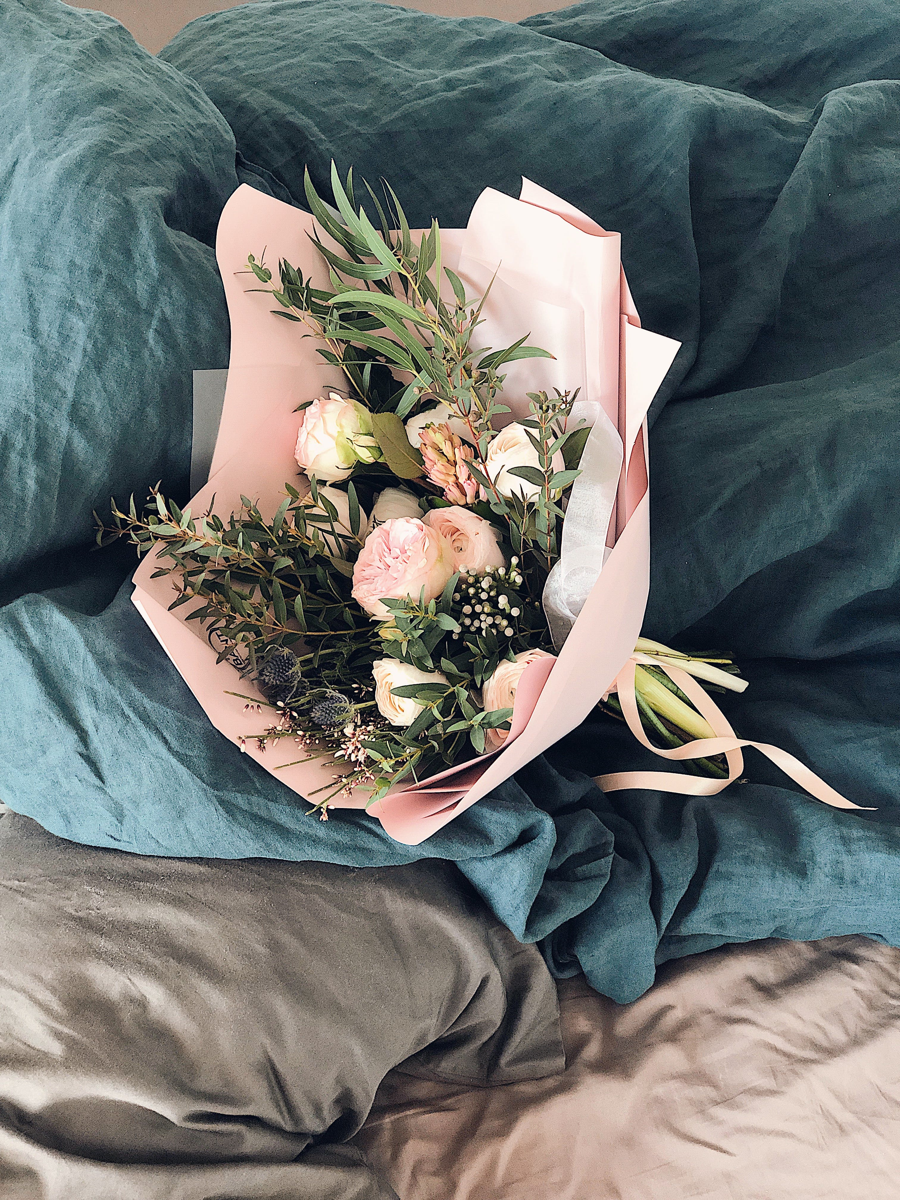 Pink and Green Flower Bouquet on Bed Sheet