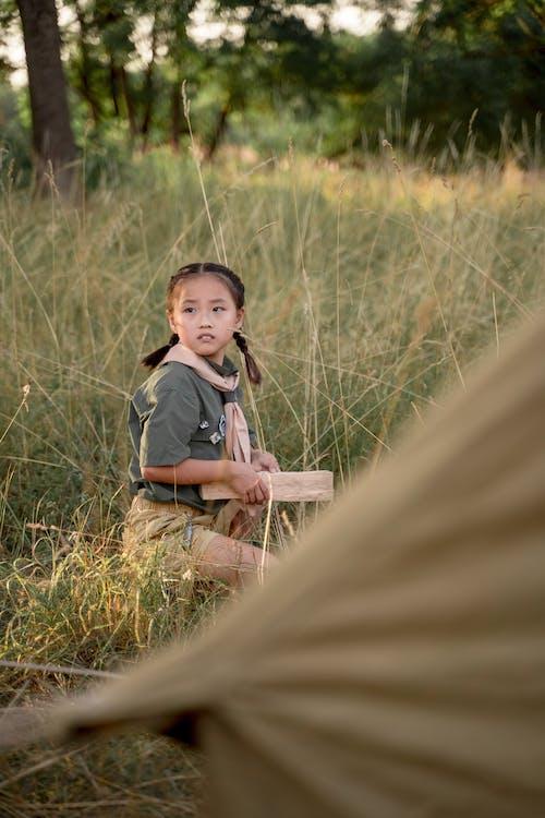 Girl Sitting on Grass Field