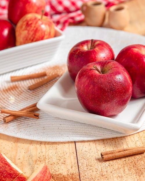 Red Apples on a Ceramic Plate Near Cinnamon Sticks