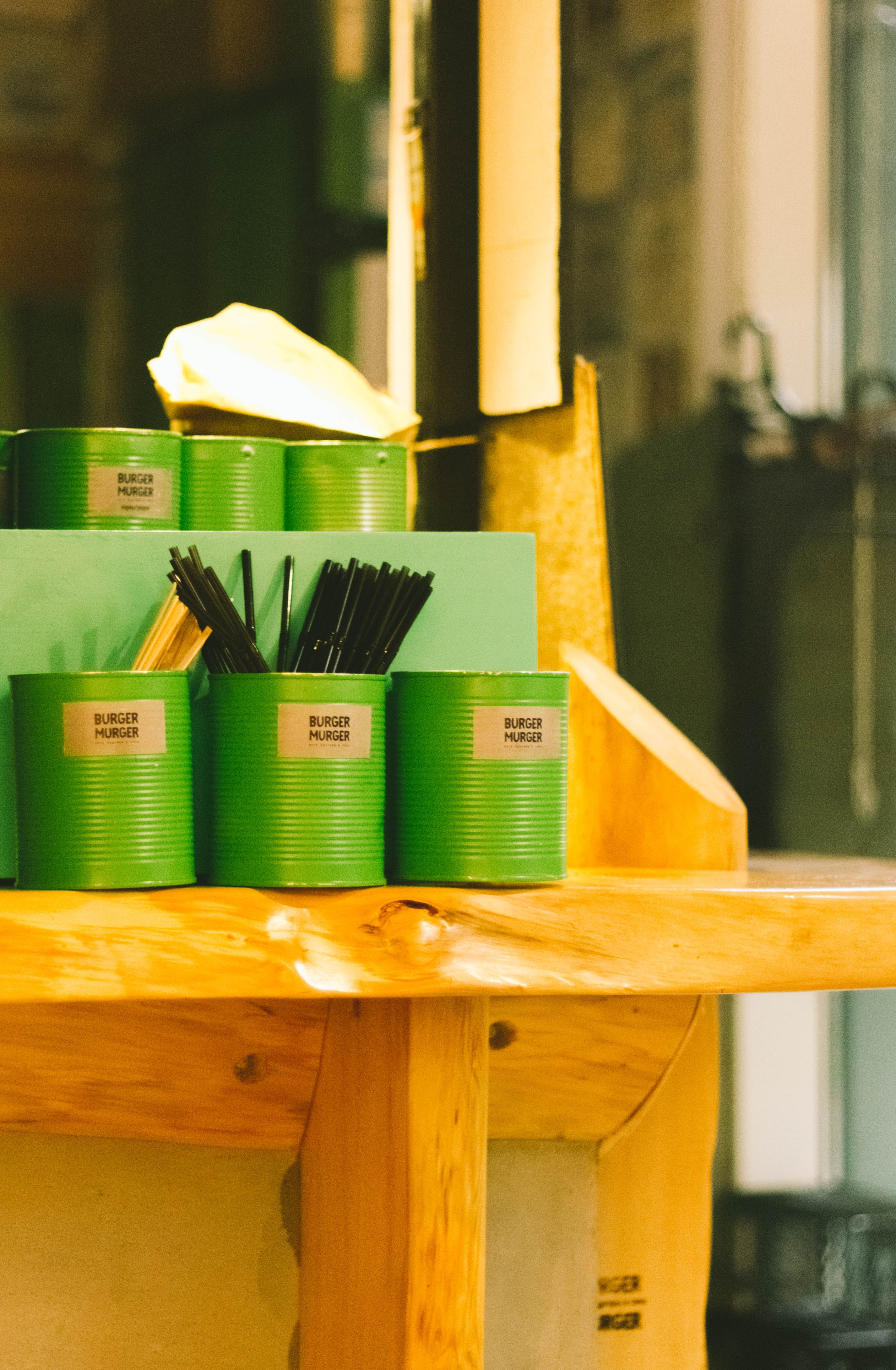 Six Green Tin Can Containers on Table