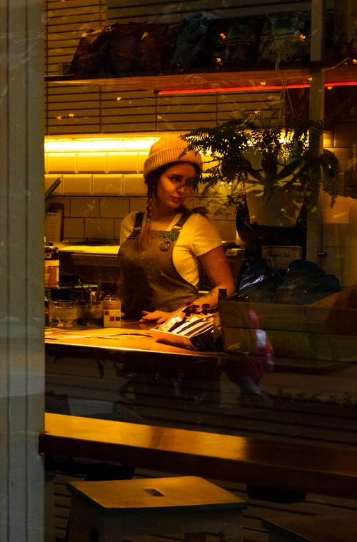 Donna Che Indossa Grembiule Marrone In Piedi Vicino Al Tavolo