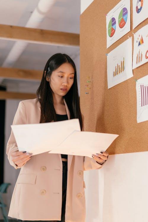 Woman in Beige Blazer Holding White Printer Paper