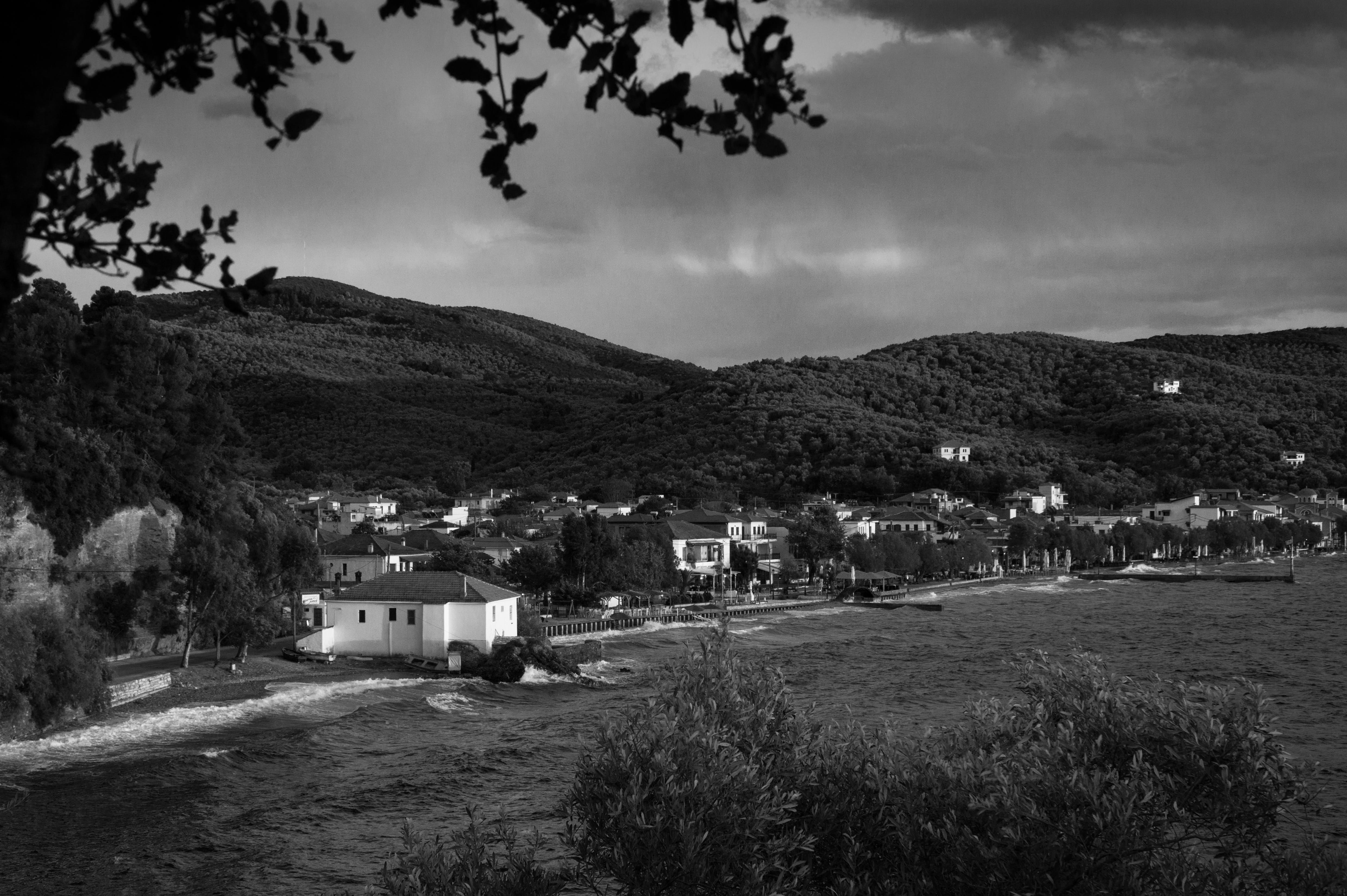 Grayscale Photo of Riverside Town Near Hills