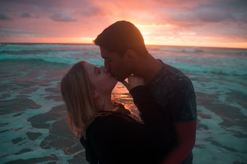 A Couple Kissing on the Shore during Sunset