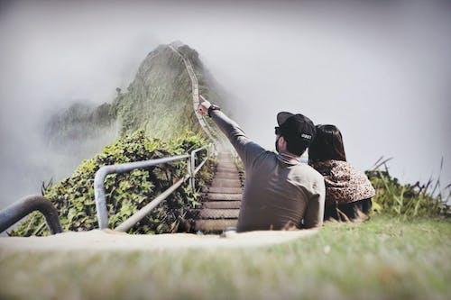 Photography of Couple Sitting on Green Grass Near Bridge