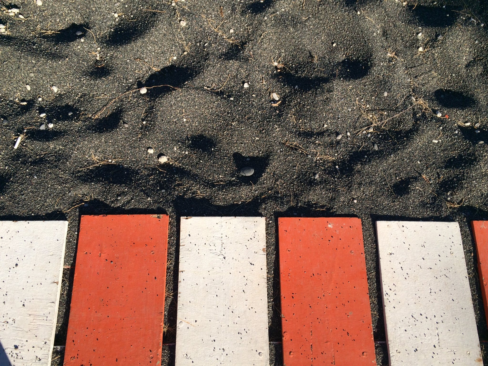 Red and White Metal Planks on Black Sand