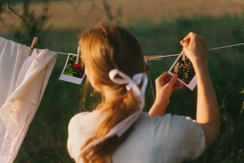Eine Person Hängt Polaroidfotos An Einer Wäscheleine