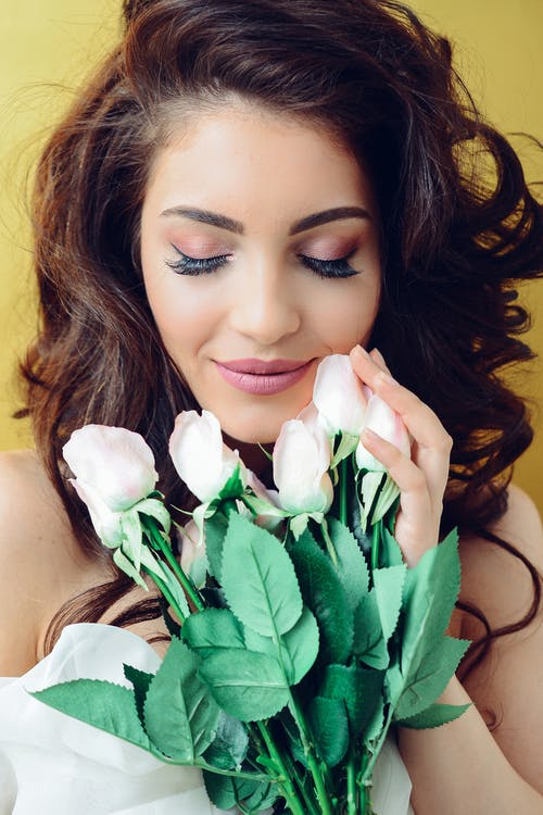 Photography of a Woman Holding White Flowers