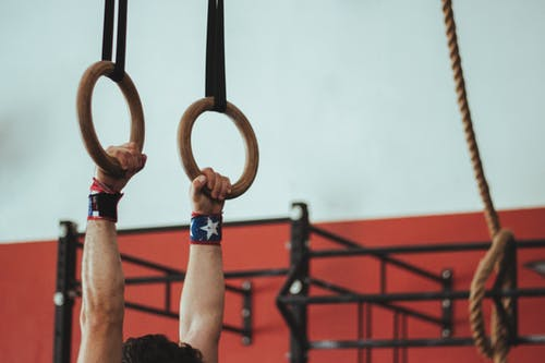 Male Gymnast Holding On To Two Wooden Rings